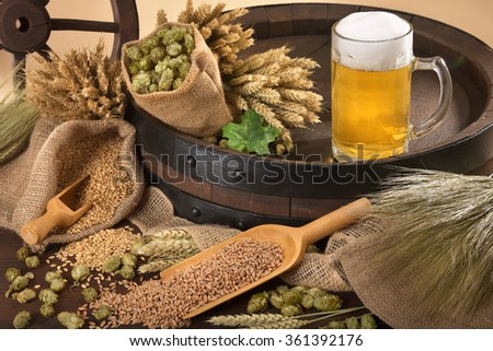 beer barrel, beer glass with hops, wheat, grain, barley and malt - stock photo