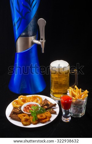 Beer barrel with beer glasses and Potatoes fries, Deep batter fried squid rings and  peanuts on dark background. - stock photo