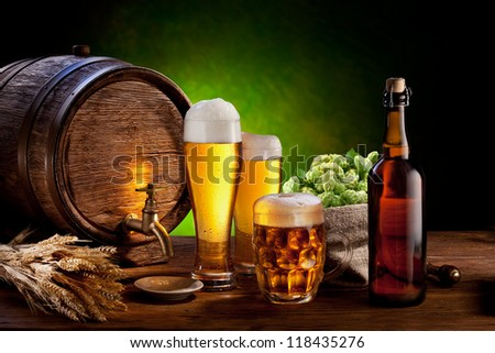 Beer barrel with beer glasses on a wooden table. The dark green background. - stock photo