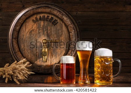 Beer barrel with beer glasses on wooden background - stock photo