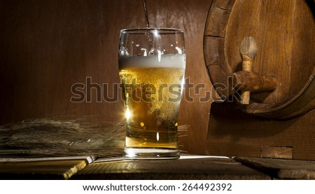 Beer barrel with beer mug on a wooden dark background. - stock photo