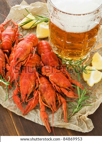Beer, boiled crawfish with lemon and rosemary. Viewed from above. - stock photo