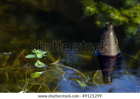 Beer bottle floats in a ditch.  Bottle is half submerged and littered the stagnant water in a North Louisiana ditch. - stock photo