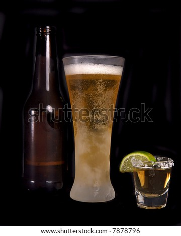 Beer bottle, frosty glass of beer and a shot of tequila - stock photo