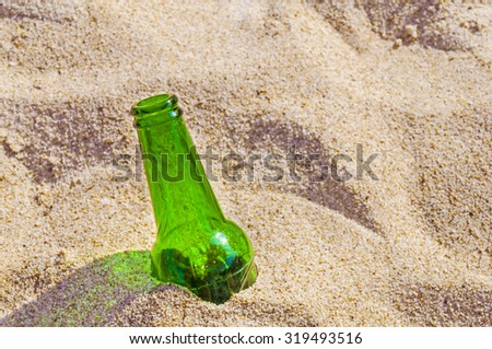 Beer bottle on a sandy beach  - stock photo