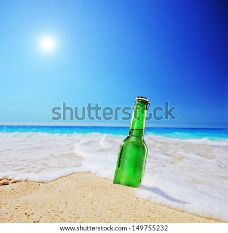 Beer bottle on a sandy beach with clear sky and wave, shot with a tilt and shift lens - stock photo