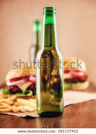 Beer bottles and burgers in the background - stock photo