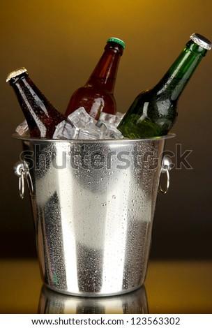 Beer bottles in ice bucket on darck yellow background - stock photo