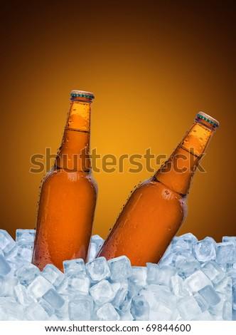 Beer bottles in ice over brown background - stock photo