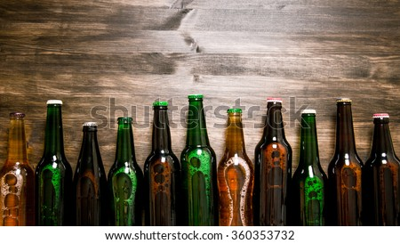 Beer bottles on a wooden table . Top view - stock photo