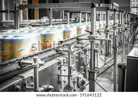 beer cans on the conveyor belt - stock photo
