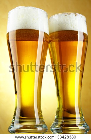 Beer close-up with froth over yellow background - stock photo