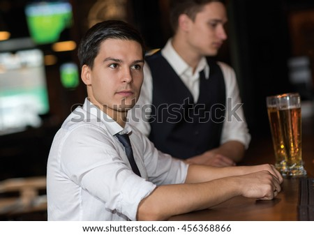 Beer evening. Young and handsome man is waiting for his beer drink in a pub. Beer pub concept