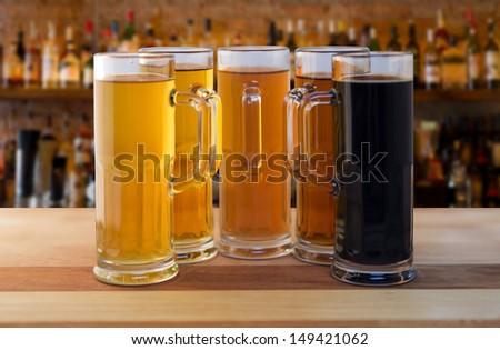 beer flight of five sampling mugs of light and dark craft beer in a bar - stock photo