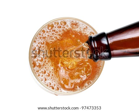 Beer flow in a glass from a brown bottle, top view - stock photo
