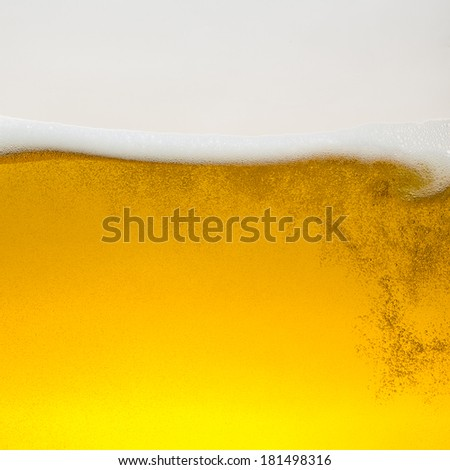 Beer foam wave on golden glass