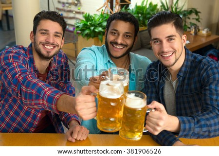 Beer friends. Top view shot of a group of friends enjoying beer at the pub smiling cheerfully  - stock photo