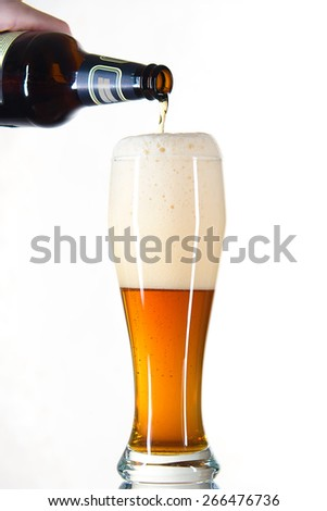 beer from a bottle poured into a glass on a white background - stock photo