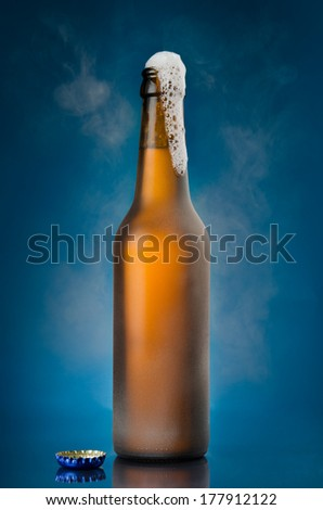 Beer frothing out of freshly opened bottle - stock photo