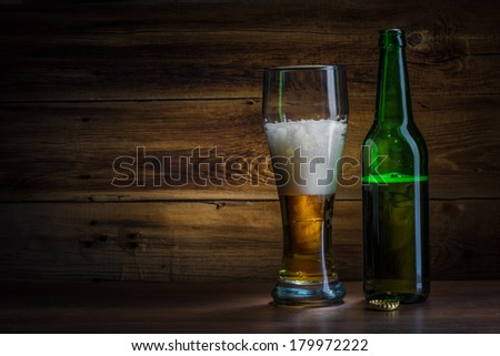 beer glass and bottle on a wooden background - stock photo