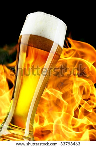 Beer glass close-up and flame in the background - stock photo