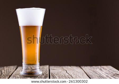Beer glass on a wooden table - stock photo