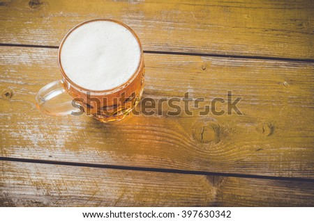 Beer glass on an old yellow wooden table. Close up - stock photo