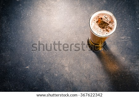 Beer glass on dark table - stock photo