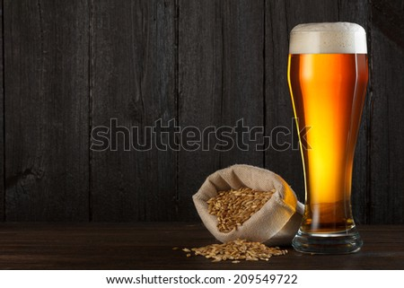 Beer glass with bag full of beer barley for brewing, on wooden table with copy space - stock photo