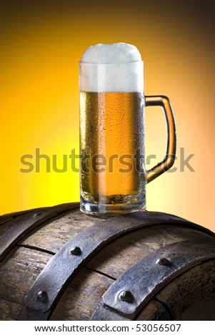 Beer glass with froth over yellow background - stock photo