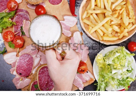Beer glass with light beer with foam, male hand, meat on the board, lettuce and french fries.