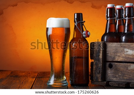 Beer glass with wooden crate full of beer bottles on table - stock photo