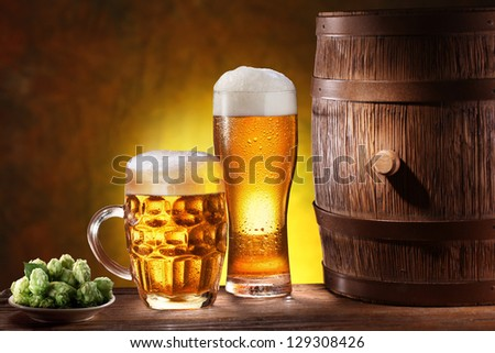 Beer glasses with a wooden barrel. Background - dark yellow gradient. - stock photo