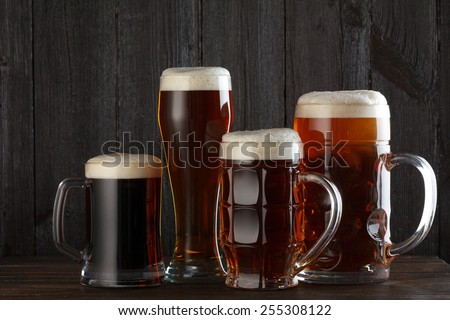 Beer glasses with lager, dark lager, ale, stout beer on table, dark wooden background - stock photo