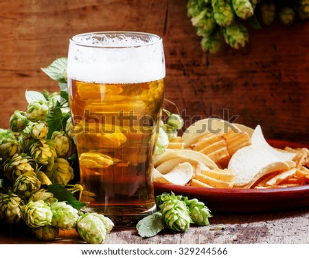 Beer in a glass, chips on the plate, bunch of fresh hops, on the old wooden background, selective focus - stock photo