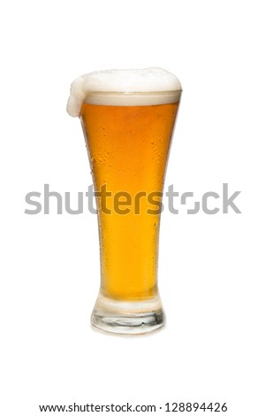 Beer In a pilsner glass with foam top isolated against white background.