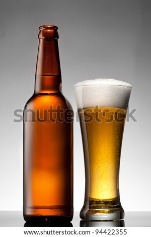 Beer in glass and bottle on white - stock photo