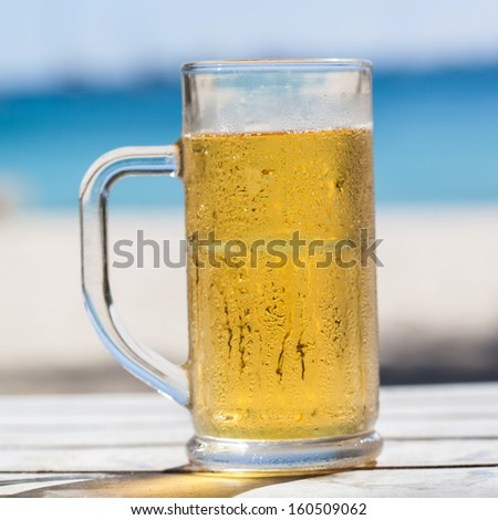 Beer in glass on a beach
