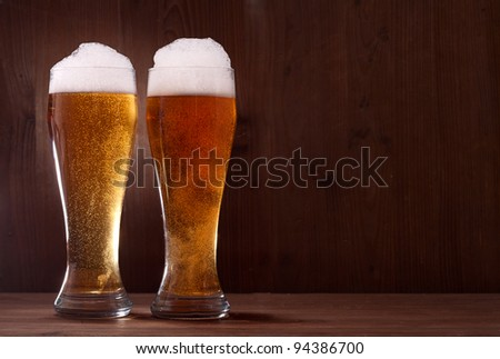 beer in glass on wooden background - stock photo