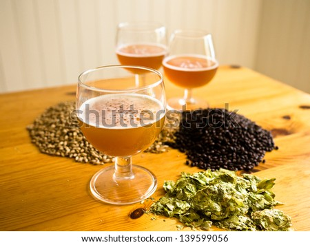 Beer in glasses, hops and malt displayed on table - stock photo