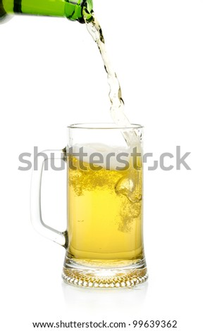 Beer is poured from a green bottle into a glass, isolated on white