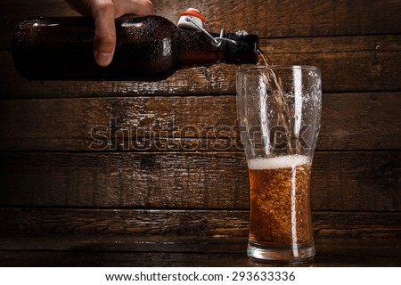 Beer is pouring into a glass over wooden background - stock photo
