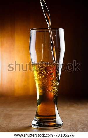 Beer is pouring into glass - stock photo