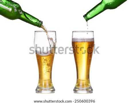 Beer is pouring into glass from bottle isolated on white background. Beer make splash - stock photo