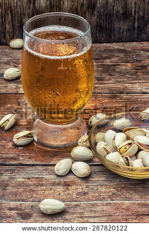 beer light beer on wooden table with saucer of salted pistachios.Photo tinted.Selective focus - stock photo