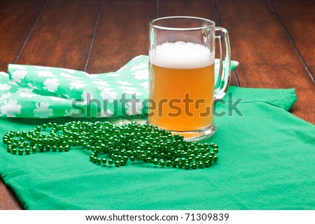 Beer mug, beads, bottle opener on a green material on wooden table. - stock photo