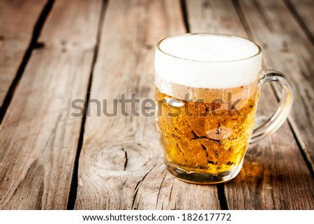 Beer mug on rustic vintage planked wood table. Background layout with free text space. - stock photo