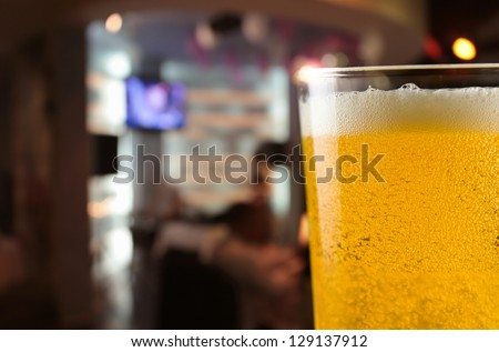 Beer mug with froth on a table in bar - stock photo