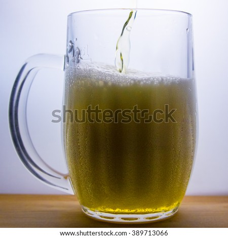 beer mug with light beer pour - stock photo