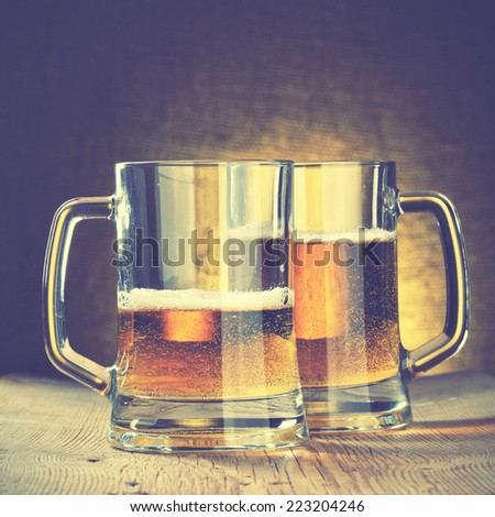 Beer mugs on the wooden table. Instagram style filtred image - stock photo